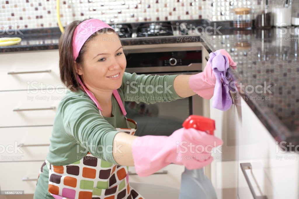 Smiling woman in gloves cleaning a white cabinet royalty-free stock photo