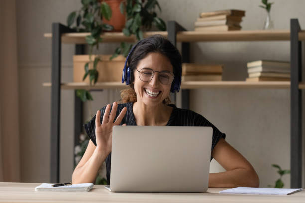 Smiling woman in headphones greeting talking on video call stock photo