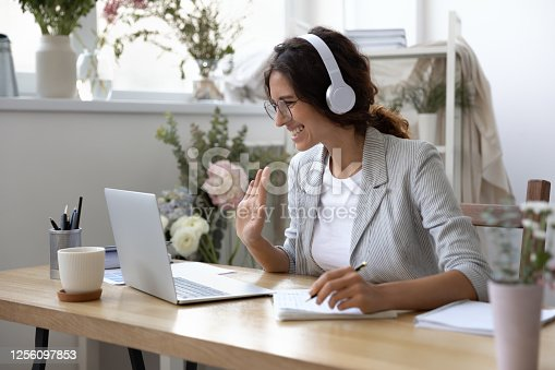 Smiling young Caucasian woman in headphones take online educational course or training on laptop from home, happy female in wireless headset wave to camera, talk on webcam video call on computer