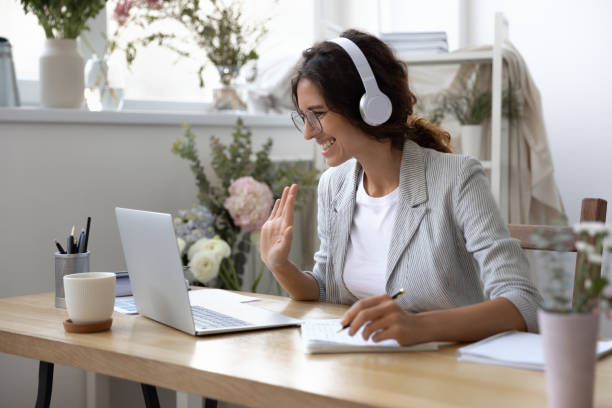 Smiling woman in headset have inline educational course Smiling young Caucasian woman in headphones take online educational course or training on laptop from home, happy female in wireless headset wave to camera, talk on webcam video call on computer video call stock pictures, royalty-free photos & images
