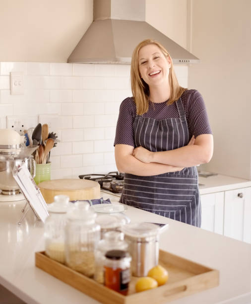 Smiling woman in her kitchen stock photo