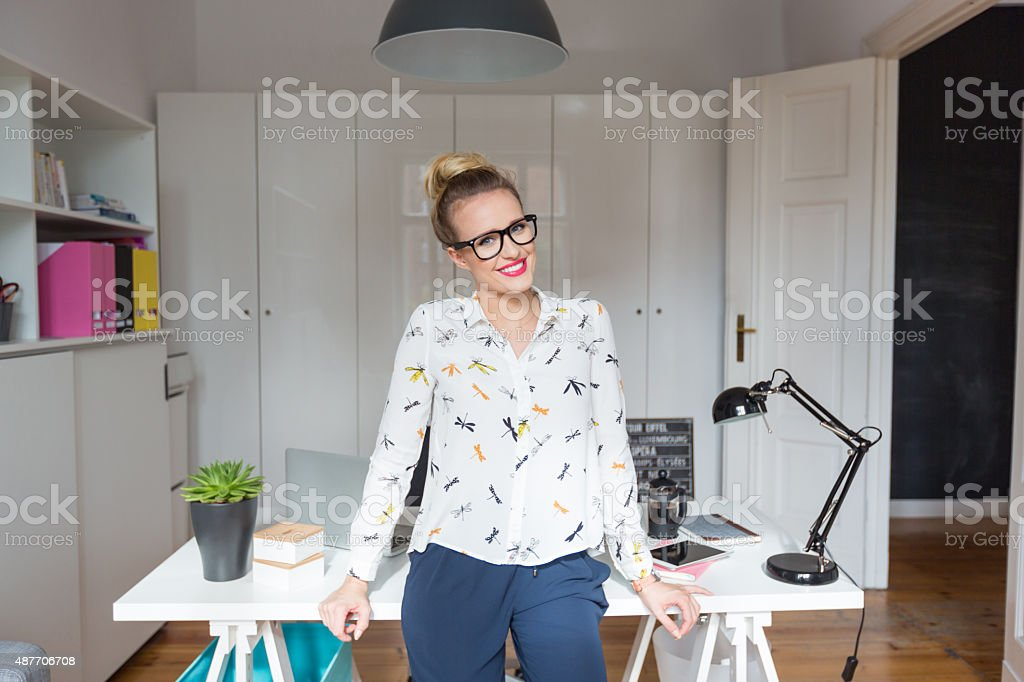 Smiling woman in home office Happy blonde woman wearing white shirt and nerd glasses standing by the desk in an office and smiling at camera. 2015 Stock Photo