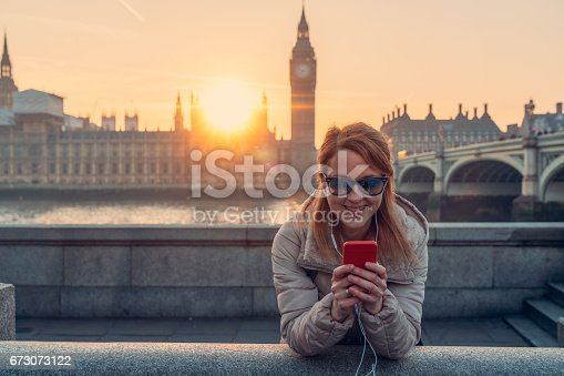 istock Smiling woman in London texting 673073122