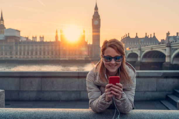smiling woman in london texting - uk travel stock photos and pictures