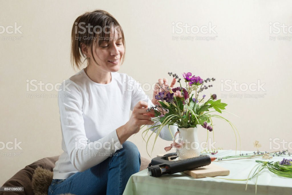 Smiling woman in process of diy flower bouquet crafting stock photo