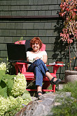 Smiling Woman In Red Chair With Laptop
