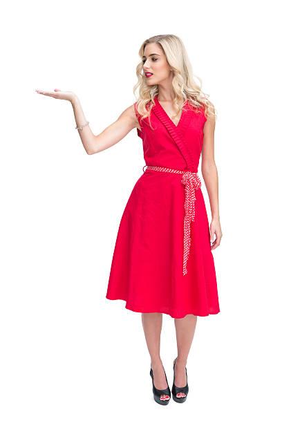 lächelnde frau im roten kleid präsentieren etwas - wickelkleid lang stock-fotos und bilder