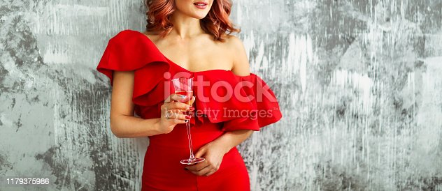 istock Smiling woman in red dress with a glass of champagne. Party concept 1179375986