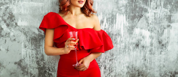 Smiling woman in red dress with a glass of champagne. Party concept stock photo