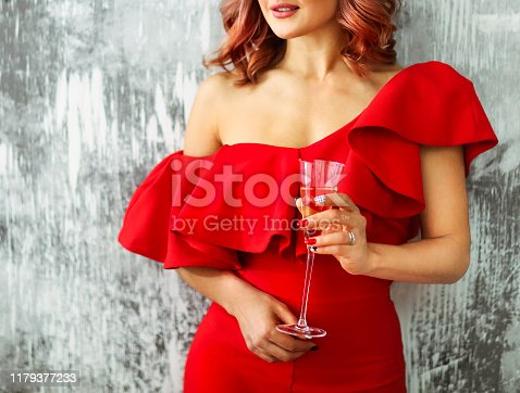 istock Smiling woman in red dress with a glass of champagne. Party concept 1179377233