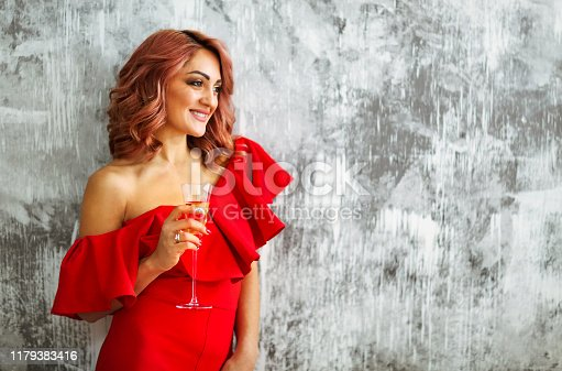istock Smiling woman in red dress with a glass of champagne. Party concept 1179383416