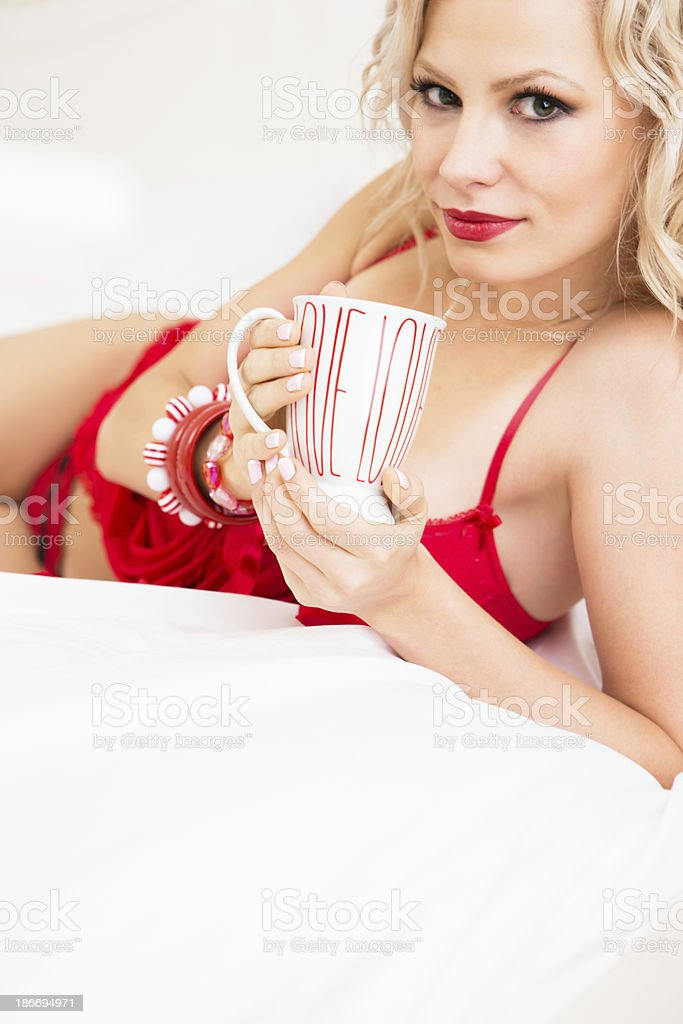 Smiling woman in red lingerie drinking coffee royalty-free stock photo