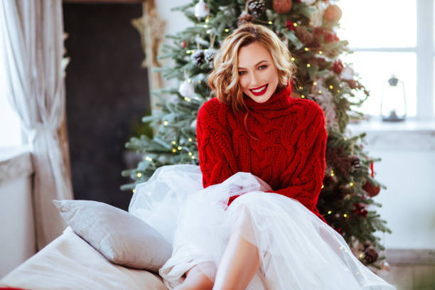 smiling woman in red sweater over christmas tree background - makeup fashion stock pictures, royalty-free photos & images