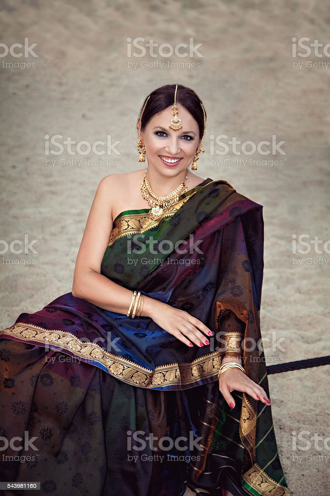 Smiling woman in sari with oriental makeup and jewelry stock photo