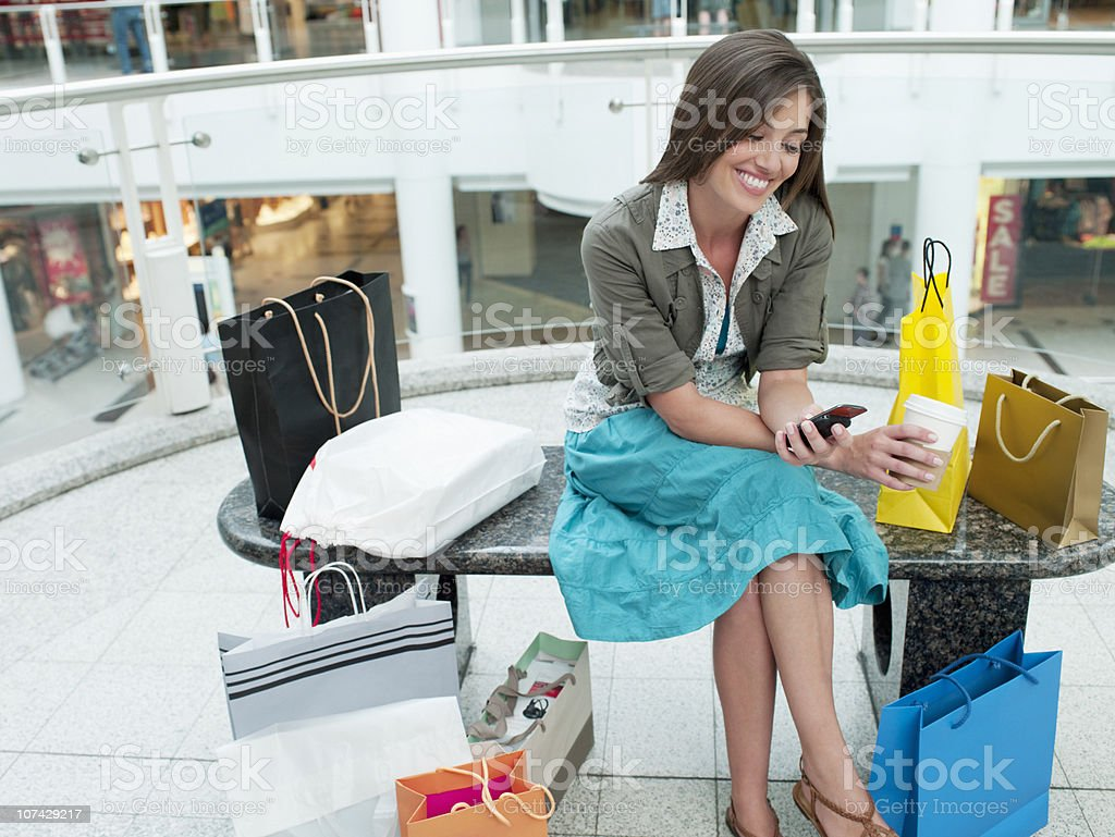 Smiling woman in shopping mall relaxing on bench royalty-free stock photo