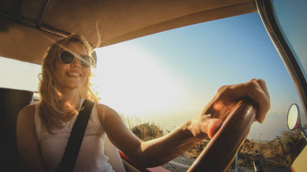 Smiling woman in sunglasses with blond hair drives car stock photo