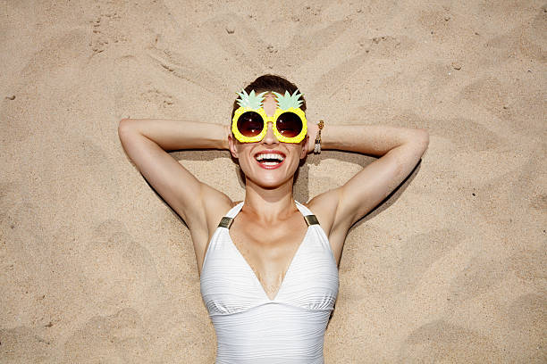 Smiling woman in swimsuit and pineapple glasses laying on sand stock photo