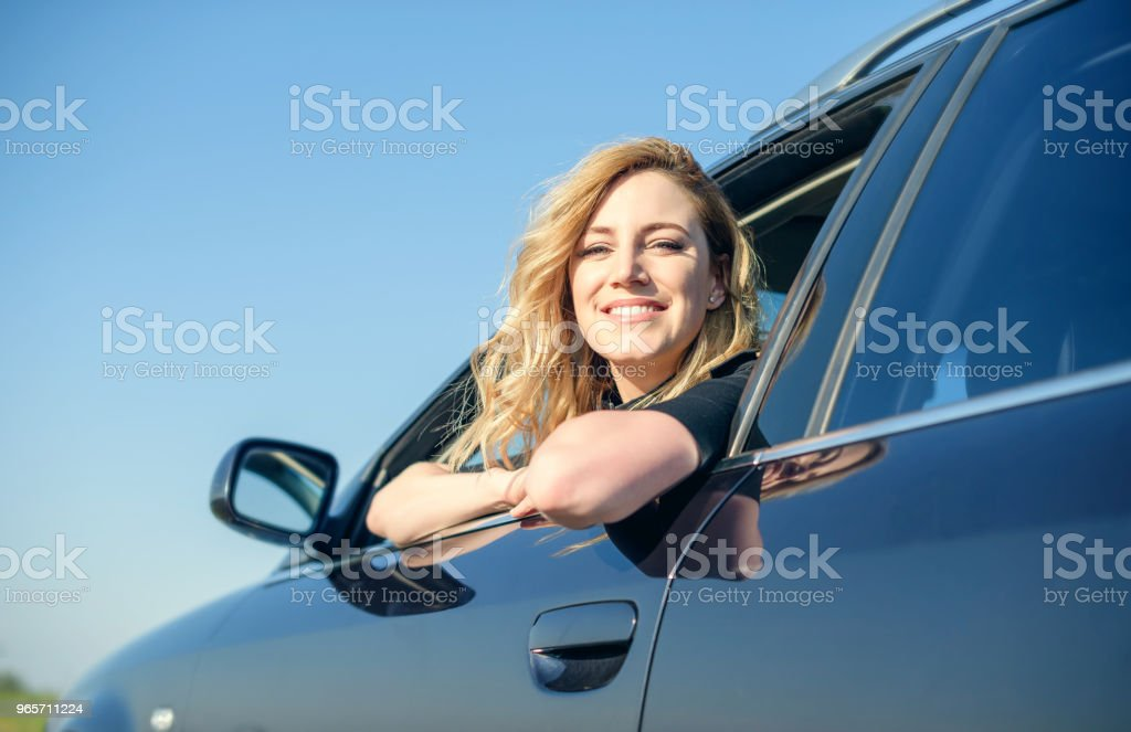 Smiling woman in the car on a summer day - Royalty-free Adult Stock Photo