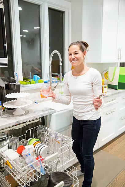 lächelnde frau in der küche im geschirrspüler füllung - backofenfenster reinigen stock-fotos und bilder