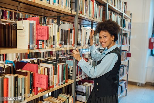 istock Smiling woman in the library 1040027756
