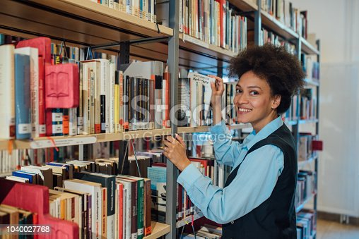 488149772istockphoto Smiling woman in the library 1040027768