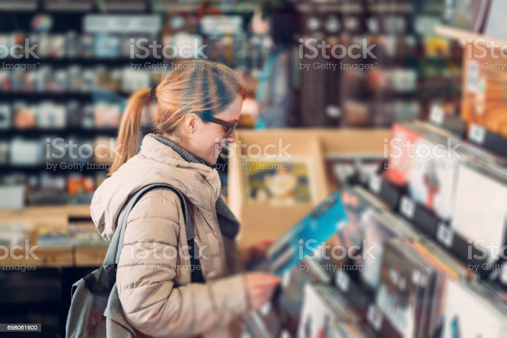 Smiling woman in the music store stock photo