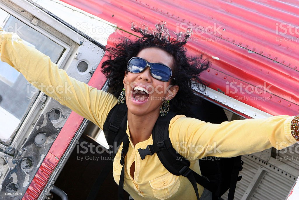 Smiling woman in yellow suit jumping out of a red plane royalty-free stock photo