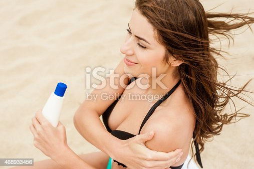 514258424istockphoto Smiling woman is applying sunblock on the beach. 468933456
