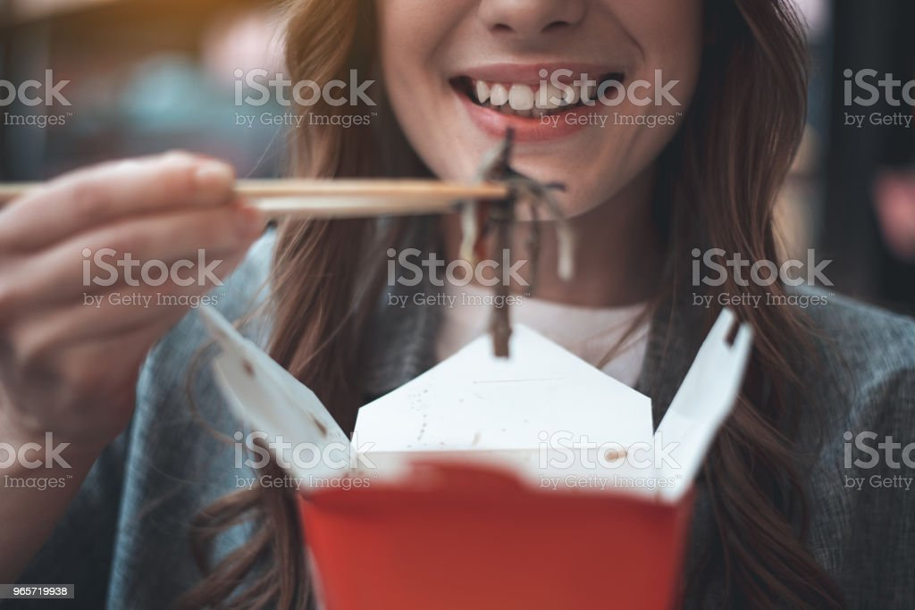 Smiling woman is eating oriental food - Royalty-free Adult Stock Photo