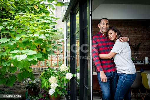 Smiling couple looking away while standing by window. Happy woman is embracing man in kitchen. They are spending leisure time.