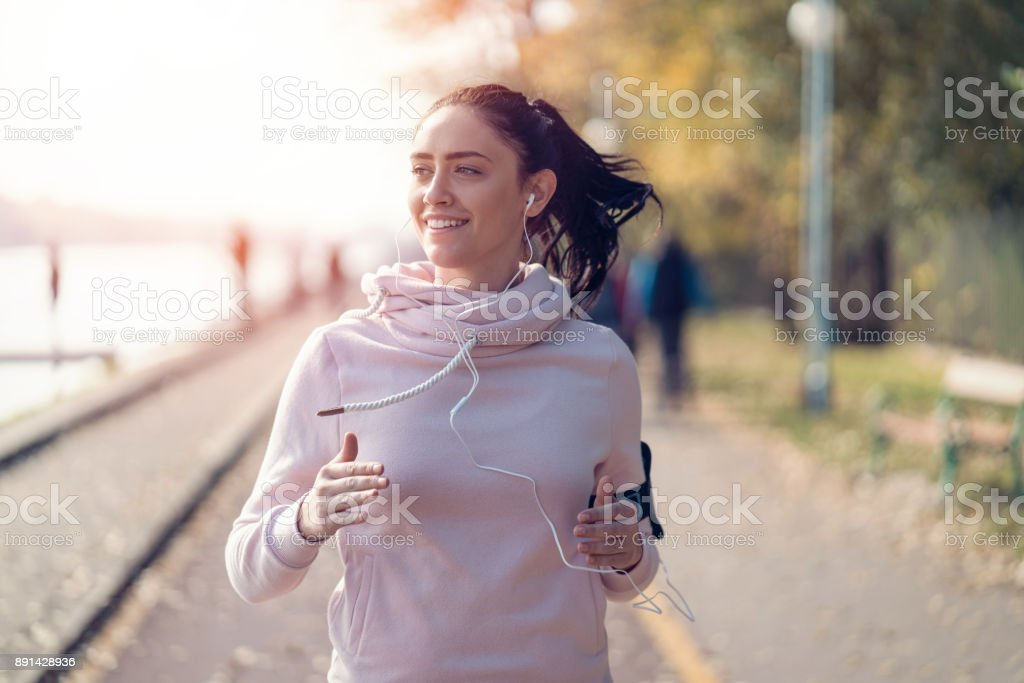 Smiling woman jogging and listening to music stock photo