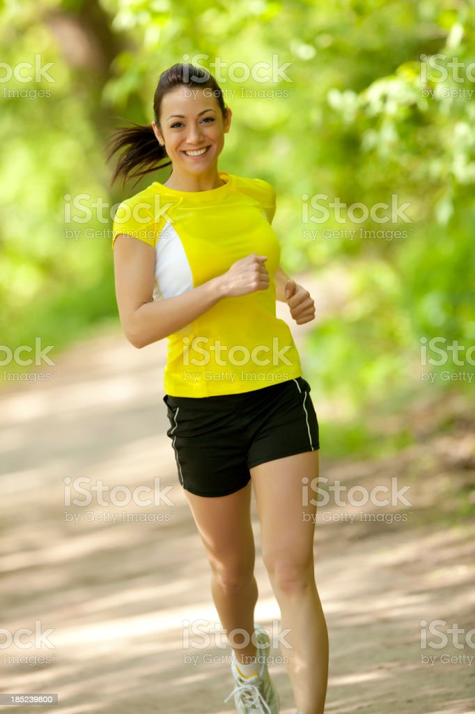 Smiling woman jogging outdoors in yellow shirt stock photo