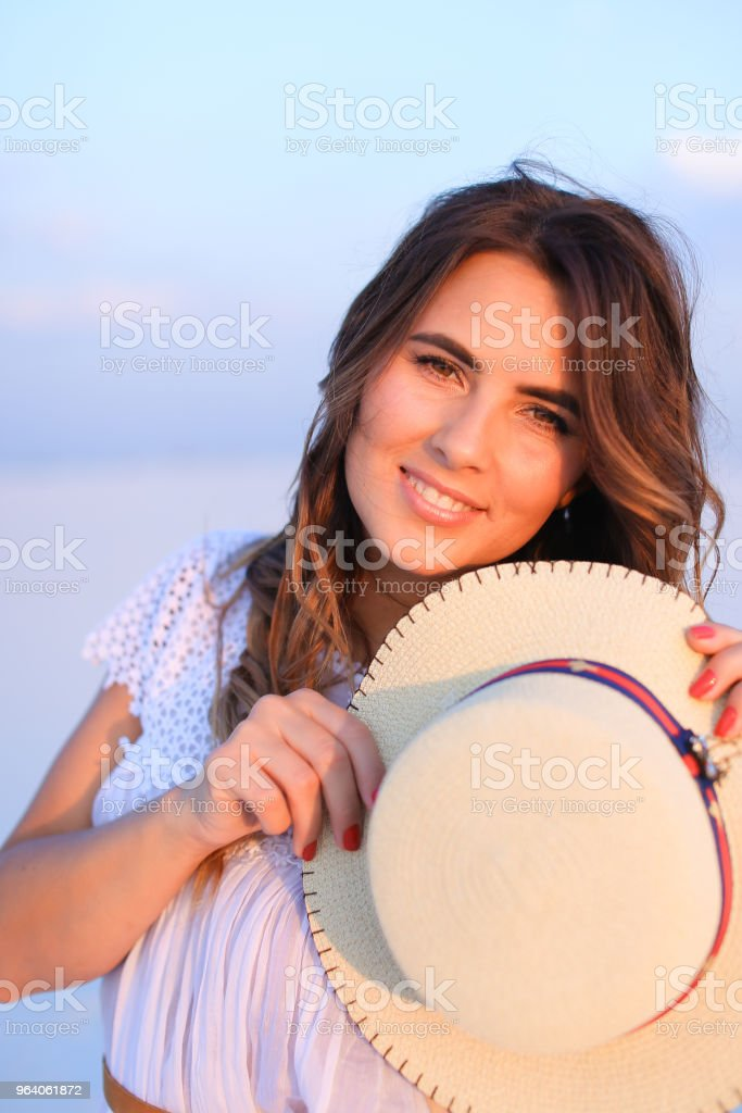 Smiling woman keeping hat in blue monophonic background - Royalty-free Adult Stock Photo