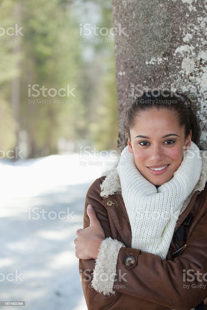 Smiling woman leaning against tree trunk in snow royalty-free stock photo