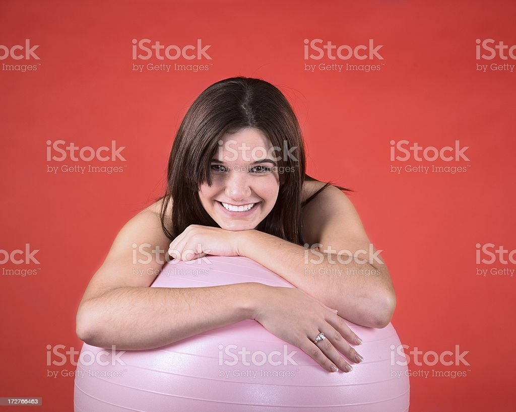 Smiling woman leaning on fitness ball on orange background. royalty-free stock photo