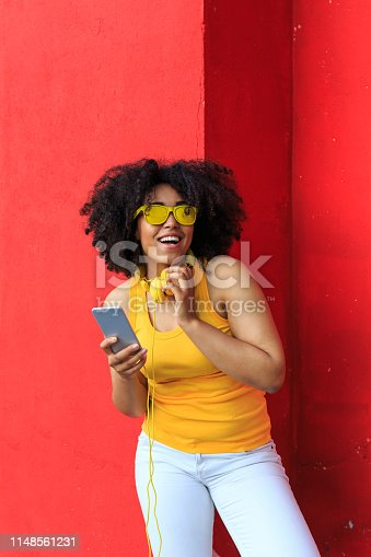 Smiling african woman standing in front of colored background and listening music.