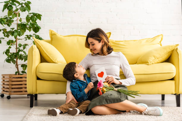 smiling woman looking at adorable son while sitting on floor with mothers day card and flowers - mothers day stock pictures, royalty-free photos & images
