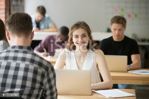 1031394390 istock photo Smiling woman looking at camera sitting at desk in co-working 912235062