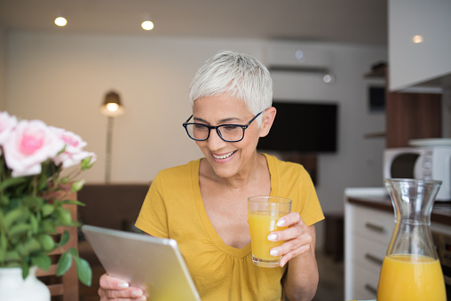 Smiling woman looking at digital tablet while drinking orange juice