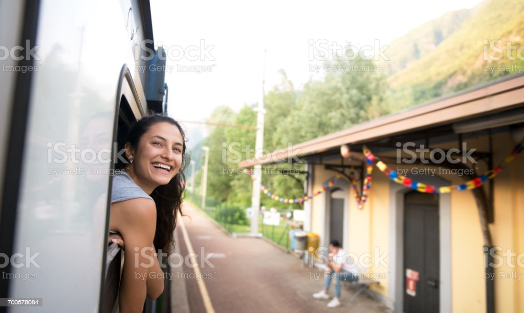 Smiling woman looking at the view from train. stock photo