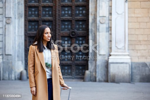 Smiling woman standing against building. Thoughtful female is wearing casuals. She is looking away.