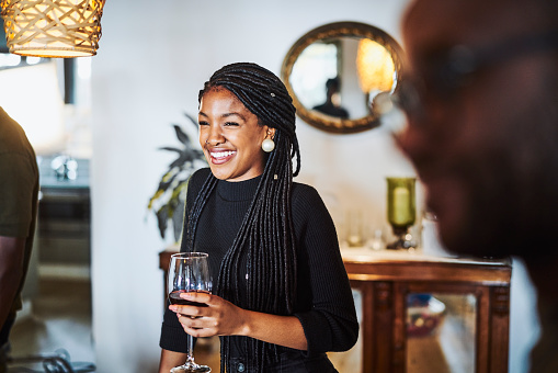 Smiling woman looking away while holding wineglass. Young female is enjoying drink in party. She is at home.