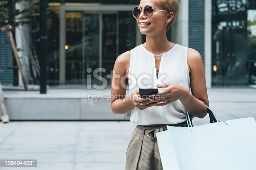 Portrait of elegant short hair blonde woman looking away and smiling. She is standing in front of shopping mall, holding smart phone and shopping bag.