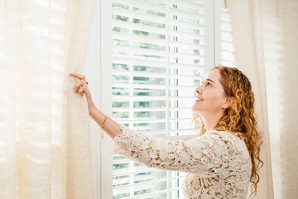 smiling woman looking out window - blinds stock pictures, royalty-free photos & images