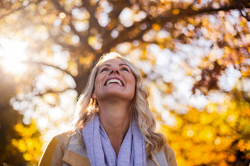 Smiling woman looking up against trees at park during autumn