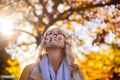 istock Smiling woman looking up against trees 629868062