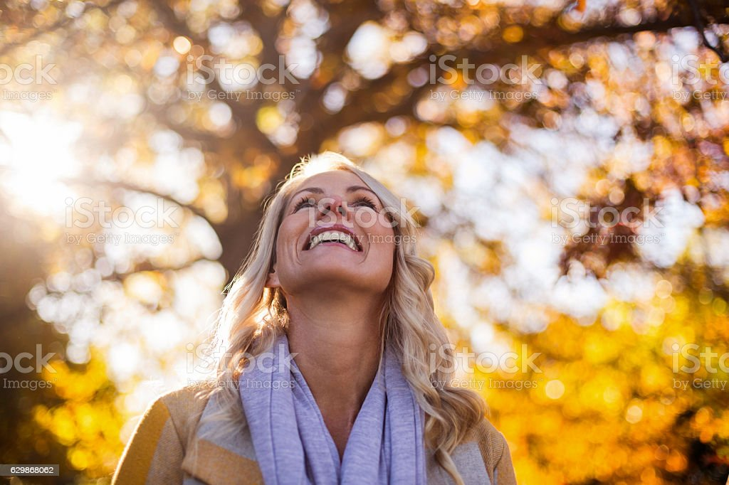 Smiling woman looking up against trees – Foto