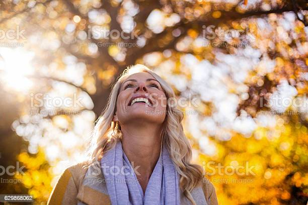 Photo of Smiling woman looking up against trees