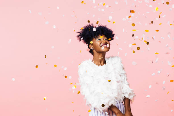 smiling woman looking up at confetti falling - carlos david stock pictures, royalty-free photos & images