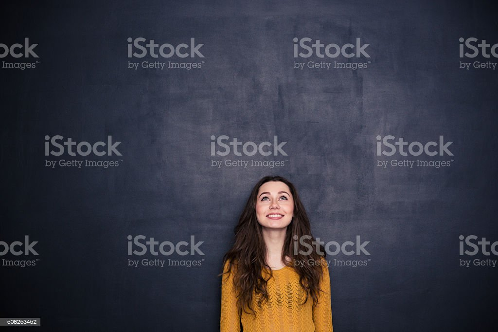 Smiling woman looking up at copyspace stock photo